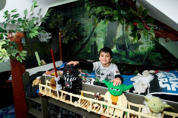Milun Simpson in his bedroom after it was transformed into a Star Wars dream room. See MASONS story MNLEGO; The Force is strong with this little Lego fan after his bedroom was transformed into a Star Wars paradise. Milun Simpson, 5, won a Lego-run competition to design his own dream bedroom - and now sleeps in an Ewok village every night. It took over 60,000 LEGO bricks to transform the bedroom into the woodland home of the cuddly characters from the blockbuster Return of the Jedi. Complete with a tree house bed, Death Star Lamp and life-size R2D2, the makeover also features a four metre long wall mural featuring a 3D Millennium Falcon spaceship.